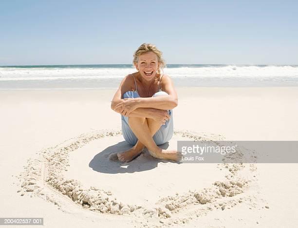 mature woman sitting on beach, laughing, portrait - 夏休み ストックフォトと画像