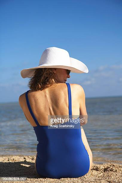 Mature woman sitting on beach, rear view, close-up