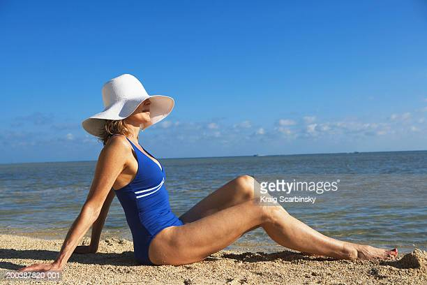 Mature woman sitting on beach, side view
