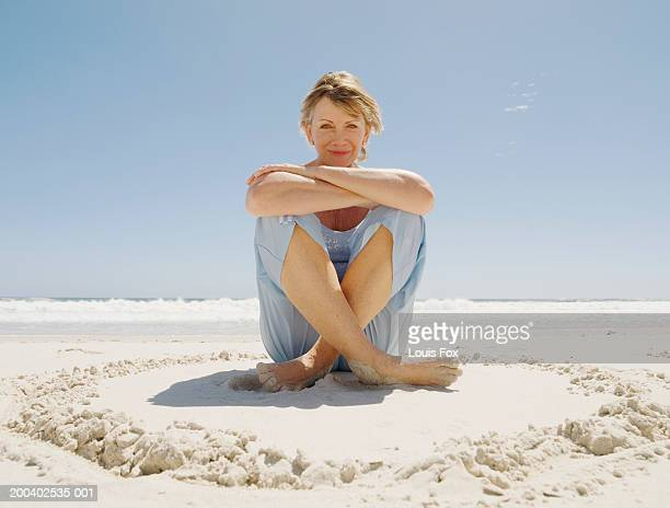 mature woman sitting on beach, smiling, portrait - one mature woman only stock pictures, royalty-free photos & images