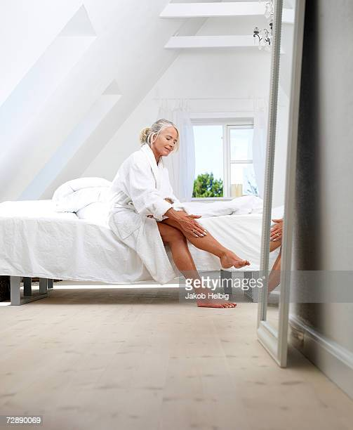 mature woman sitting on bed in bathrobe, putting cream on her leg - bathrobe stock pictures, royalty-free photos & images