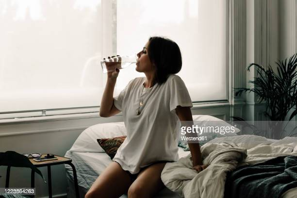 mature woman sitting on bed in the morning drinking water - dranken stockfoto's en -beelden