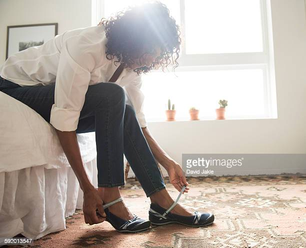 mature woman sitting on bed putting on shoes - older woman bending over stock pictures, royalty-free photos & images