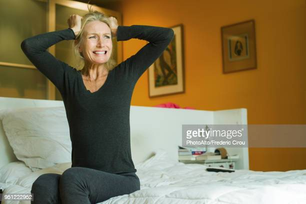 mature woman sitting on bed with hands on head in exasperation - impaciente fotografías e imágenes de stock