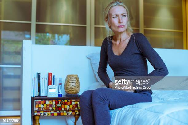 mature woman sitting on bed with hands on stomach and pained expression on face - appendicitis stock photos and pictures