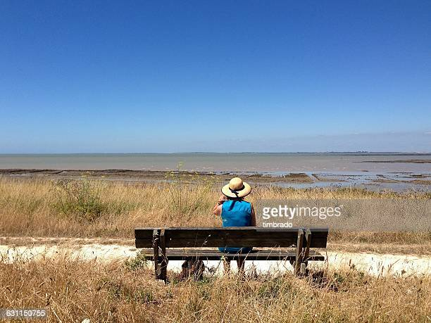 Mature woman sitting on bench by sea, Nieul-sur-Mer, La Rochelle, France