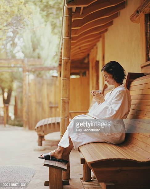 mature woman sitting on bench in white robe, holding cup - one mature woman only stock pictures, royalty-free photos & images
