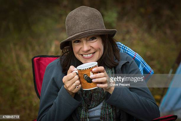 Mature woman sitting on camping chair, drinking hot drink