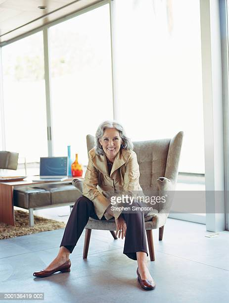 mature woman sitting on chair in house, portrait - purple shoe stock pictures, royalty-free photos & images