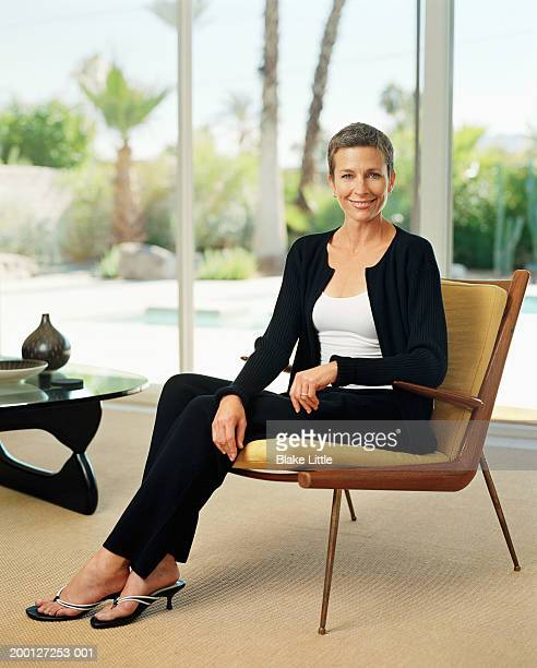 Mature woman sitting on chair in living room, portrait