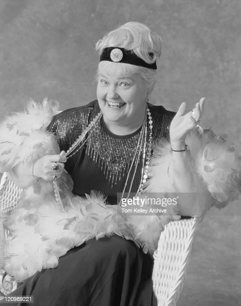 Femme d'âge mûr assis sur la chaise, souriant, portrait