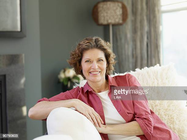 mature woman sitting on couch in loft - one mature woman only stock pictures, royalty-free photos & images