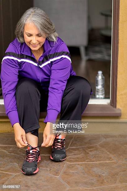 Mature woman sitting on doorstep, doing up trainers