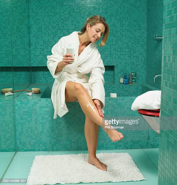 mature woman sitting on edge of bath applying cream to leg - older woman legs stock photos and pictures