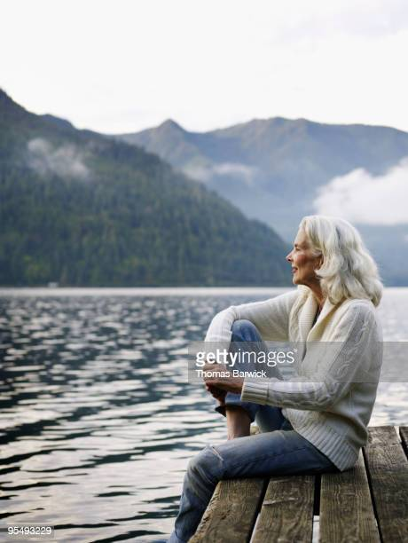 Mature woman sitting on edge of dock on lake