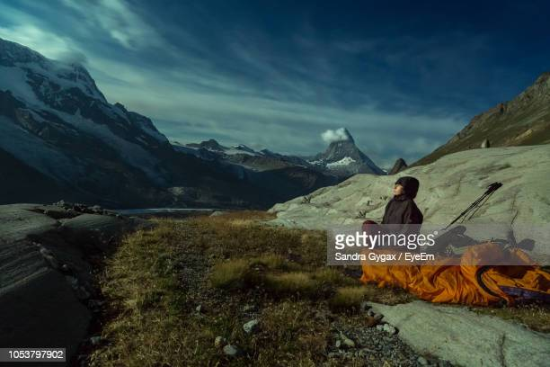 mature woman sitting on field amidst mountains against cloudy sky - sandra gygax stock-fotos und bilder