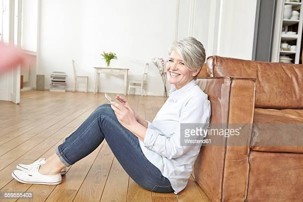 Mature woman sitting on floor using digital tablet