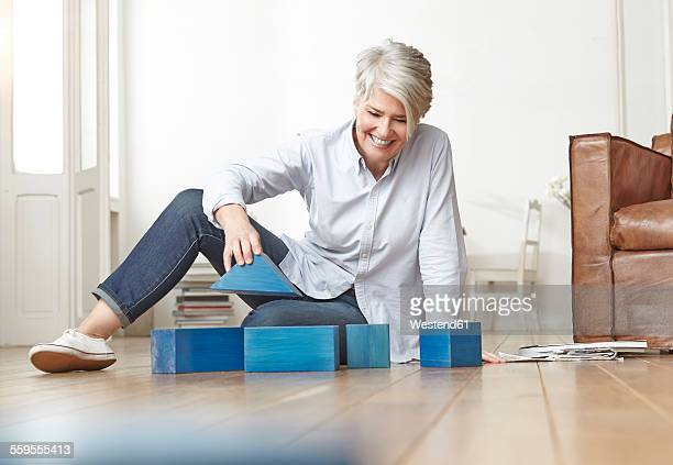Mature woman sitting on floor with building bricks