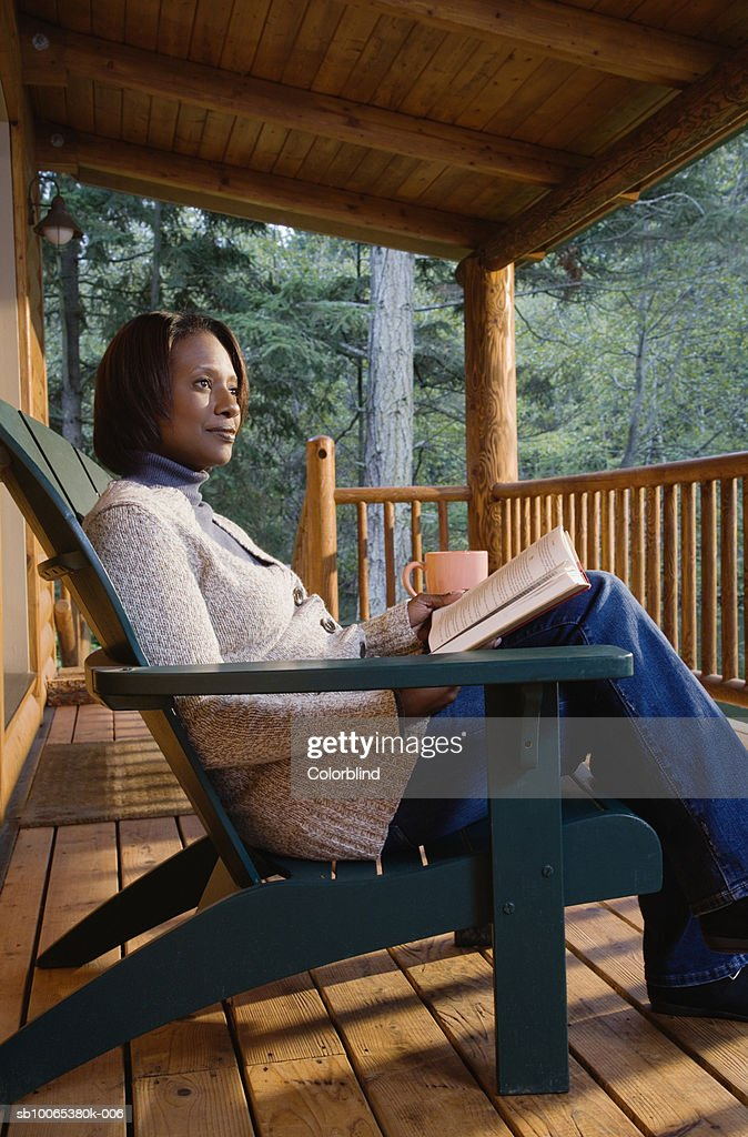 Mature woman sitting on porch, reading book : Foto stock
