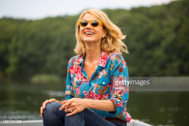 mature woman sitting on rowboat in lake - mid length hair stock pictures, royalty-free photos & images