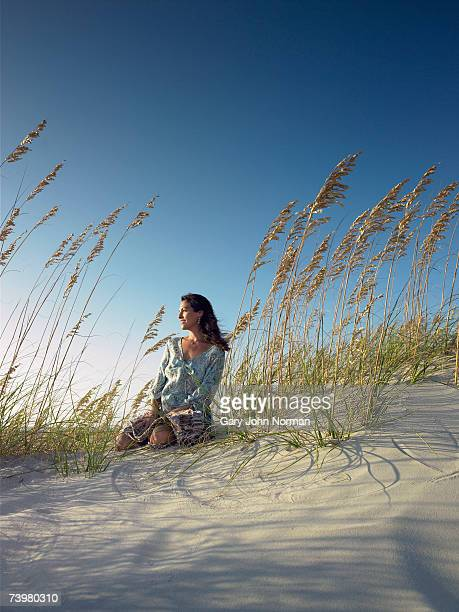 mature woman sitting on sand dune facing sun - outer banks stock pictures, royalty-free photos & images