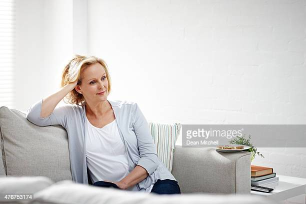 Mature woman sitting on sofa and thinking