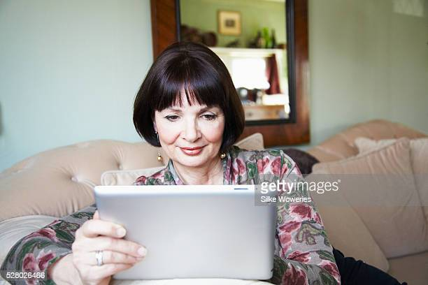 Mature woman sitting on sofa and using digital tablet