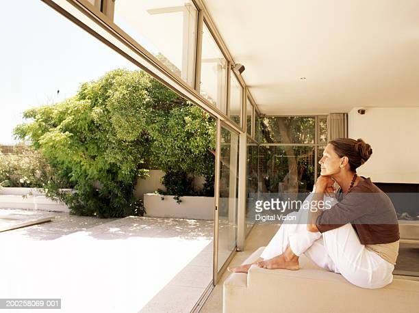 Mature woman sitting on sofa by balcony indoors, side view