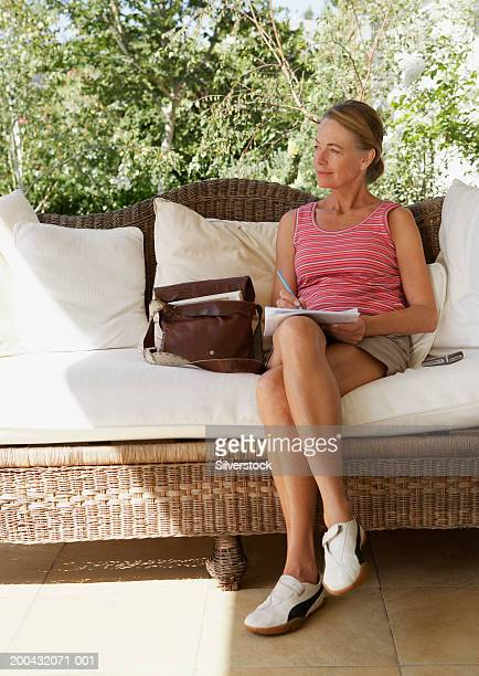 Mature woman sitting on sofa, holding paperwork and pen