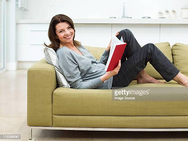 mature woman sitting on sofa reading book - femme 50 ans brune photos et images de collection