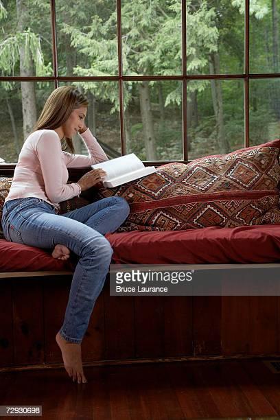 Mature woman sitting on sofa, reading book