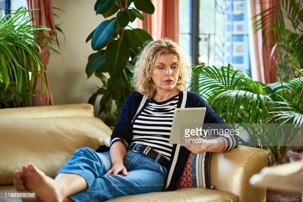 mature woman sitting on sofa with digital tablet - mature women stock pictures, royalty-free photos & images