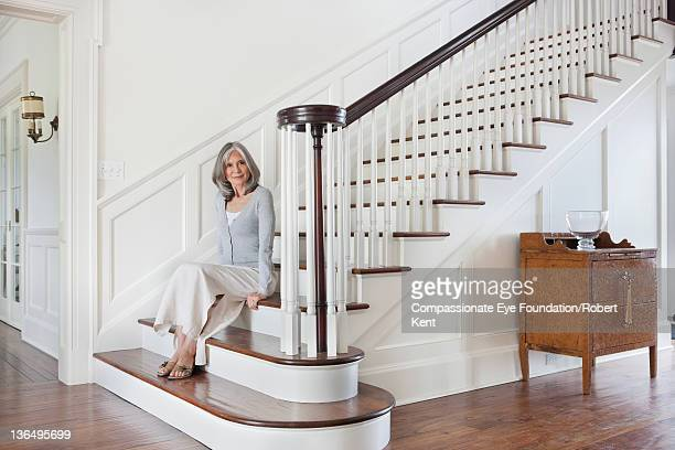 Mature woman sitting on stairs in entrance hall