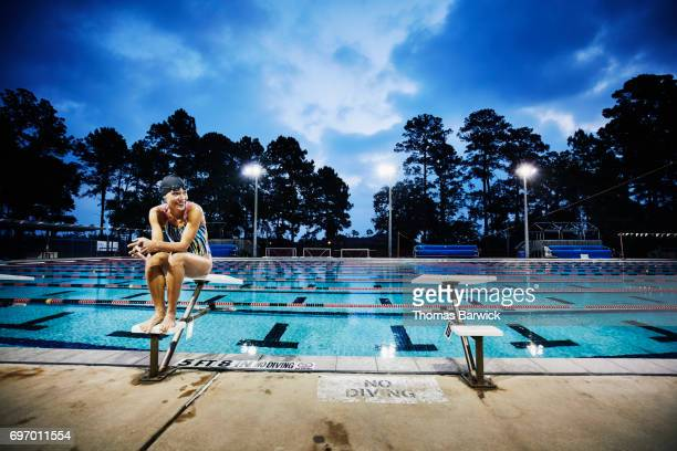 Mature woman sitting on starting block at outdoor pool before early morning workout