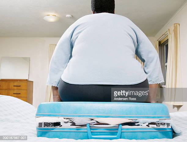Mature woman sitting on suitcase, rear view