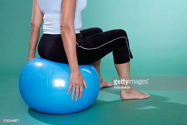 mature woman sitting on swiss ball (close-up) - vieilles fesses photos et images de collection