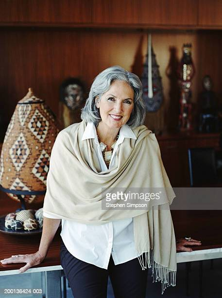 mature woman sitting on table, art pieces in background, portrait - shawl stock pictures, royalty-free photos & images