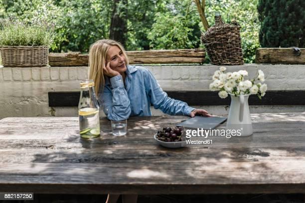 mature woman sitting on terrace, enjoying summer - natürlicher zustand stock-fotos und bilder