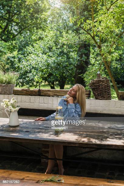 mature woman sitting on terrace, enjoying summer - one mature woman only stock pictures, royalty-free photos & images