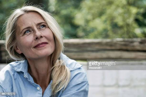 mature woman sitting on terrace, thinking - 50 54 years stock pictures, royalty-free photos & images