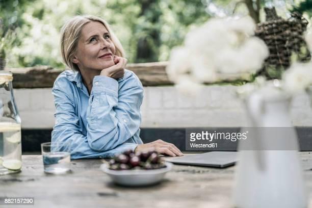 mature woman sitting on terrace, with cherries on table - zufrieden stock-fotos und bilder