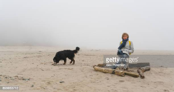 Mature woman sitting on the sandy beach of the Baltic sea, with her Bernese Mountain Dog