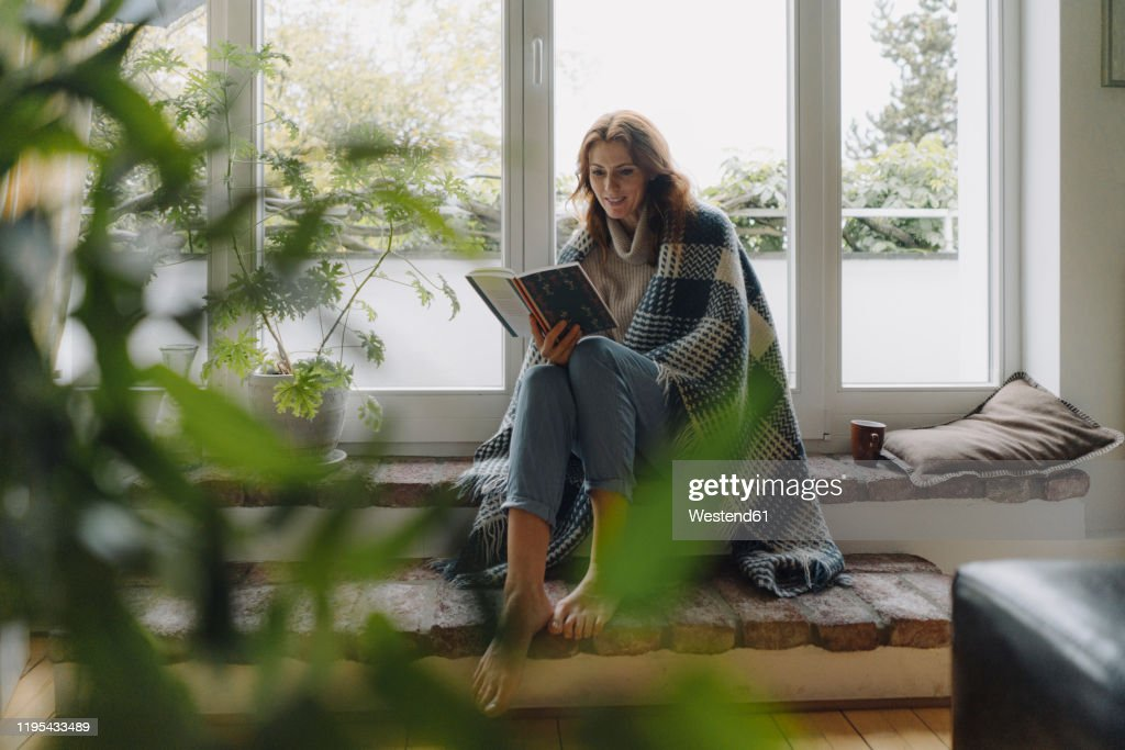 Mature woman sitting on wondow sill, wrapped in blanket, reading book : Stockfoto