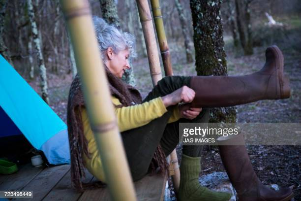 Mature woman sitting on woodland porch putting on knee high boots