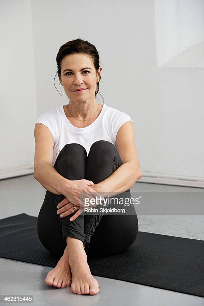 mature woman sitting on yoga mat with bare feet - old women in pantyhose stock pictures, royalty-free photos & images