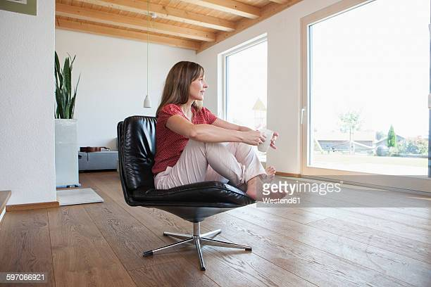 Mature woman sitting relaxed in her living room, drinking coffee