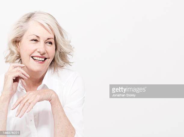 Mature woman sitting wearing in white shirt