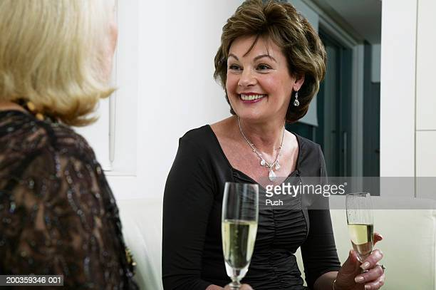 Mature woman sitting with friend, at drinks party, smiling