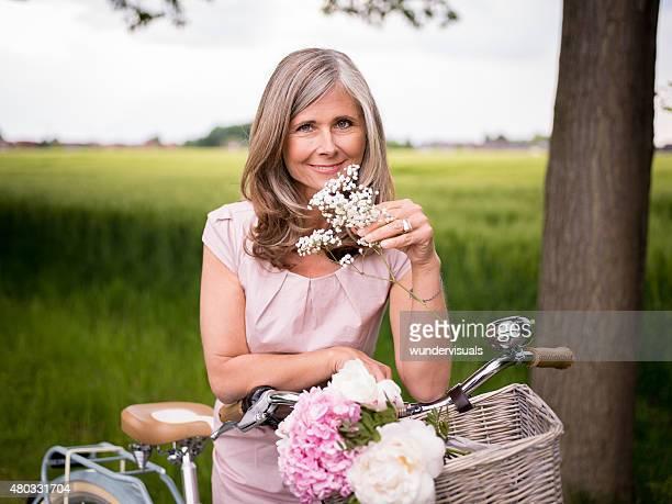 Reife Frau riechen Blumen in einem park mit ihren Fahrrädern