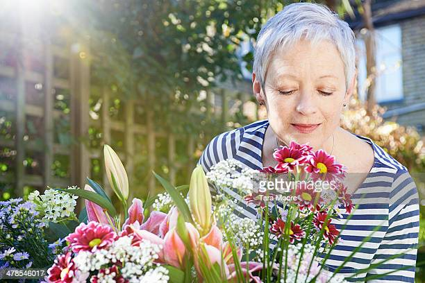 mature woman smelling flowers in garden